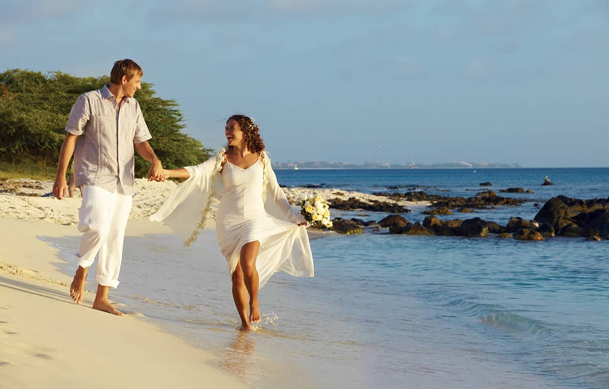 A newly wed couple running on the beach in Aruba