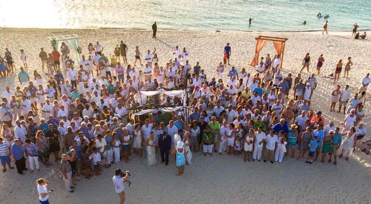 A large group of couples come together on a beach in Aruba to renew their vows.